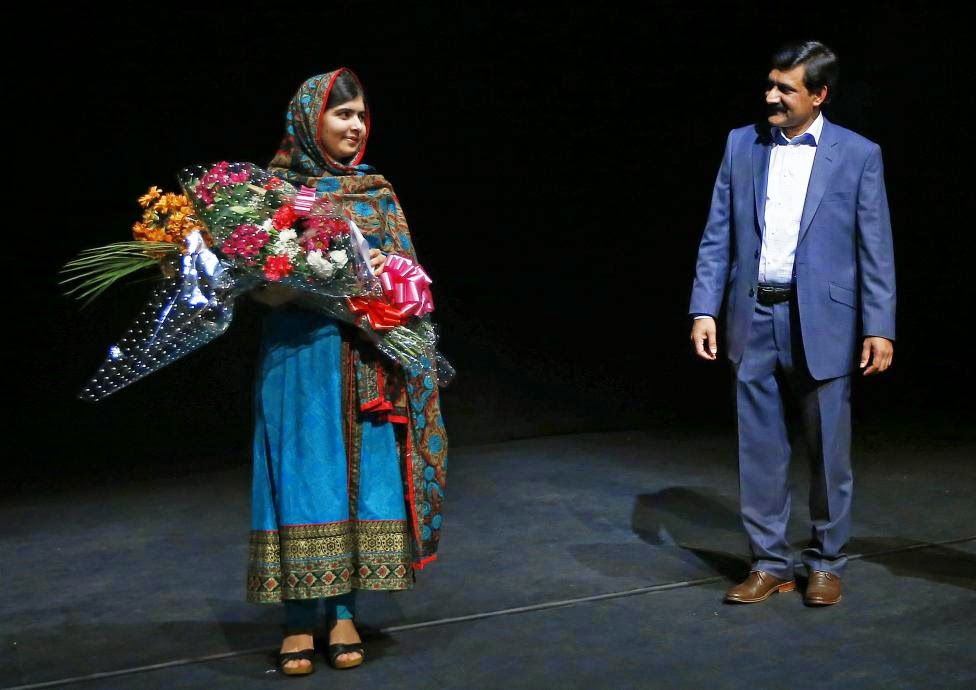 Pakistani schoolgirl Malala Yousafzai, the joint winner of the Nobel Peace Prize, stands with her father Ziauddin after speaking at Birmingham library in Birmingham, central England, October 10, 2014. REUTERS/Darren Staples