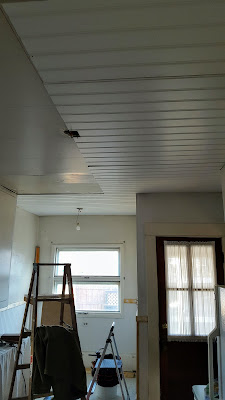Half sheets of beadboard installed on the half-complete kitchen ceiling