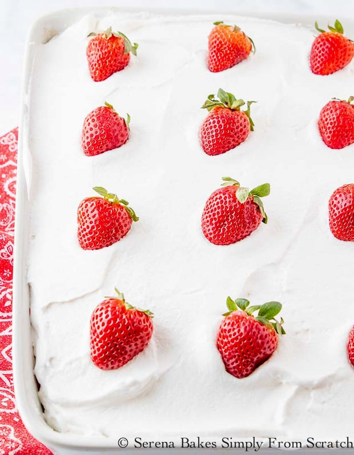 A down  shot of Strawberry Shortcake Poke Cake in a white pan covered with whipped cream and whole strawberries.