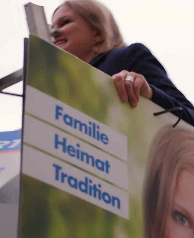 Candidata afixa cartaz pela Família, Pátria e Tradição.