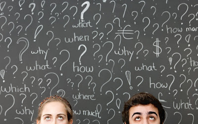 Image of two people looking up at a chalkboard with question marks and words text:which what why when how how much $