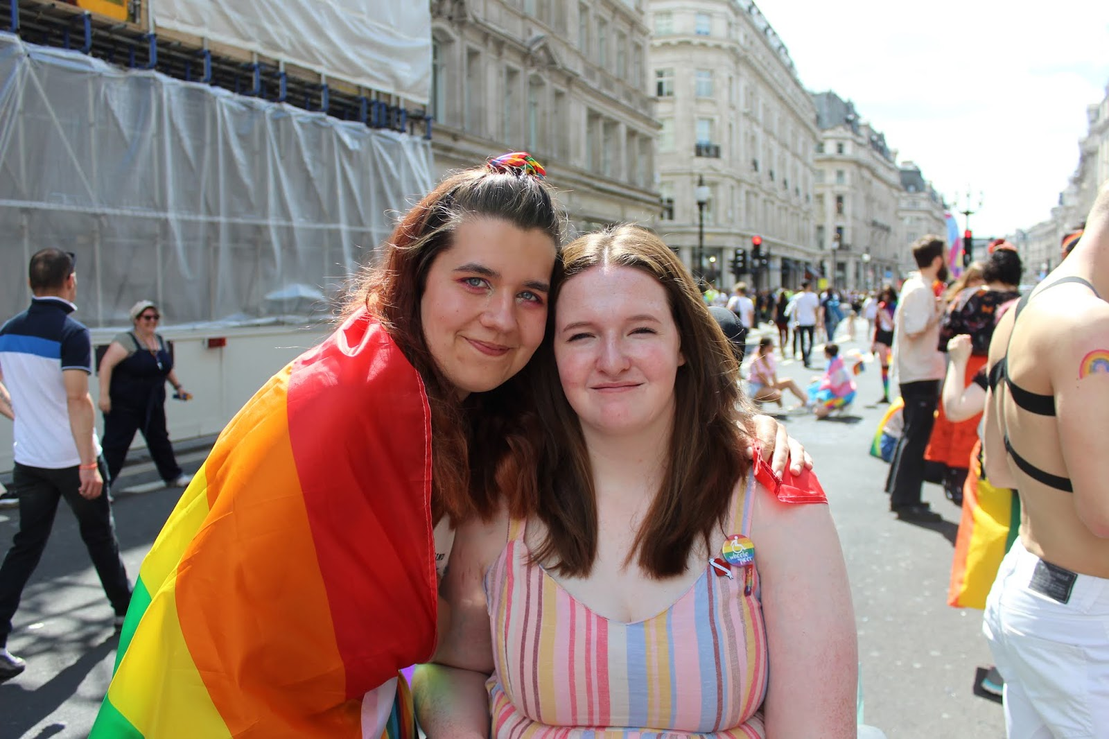 2 women at London Pride, they have a pride flag drapped across them both.