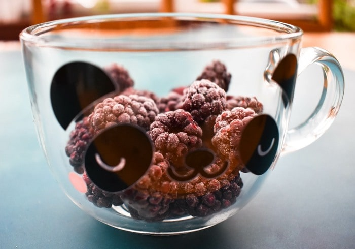 Frozen blackberries in a glass mug