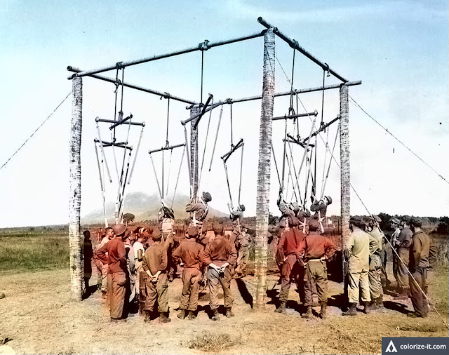 Replacement soldiers learned how to jump using this makeshift contraption.  Image source:  US National Archives. Colorized courtesy of Algoritnmia.