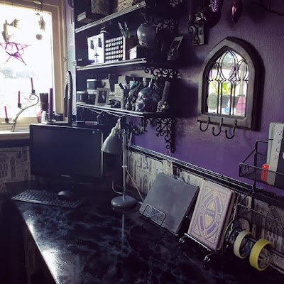 A photograph looking along a faux-marble desk towards a window and corner. The window is so bright that it looks mostly white, with a purple pentagram lantern barely visible. There is a curly black wrought iron candle-stick on the window-ledge, with three small purple candles in sockets each slightly higher than the one before, and the purple candles are at slightly jaunty angles. There is a small purple vase on the window-ledge with incense sticks. Several wind-chimes hang in the window, indistinct in the bright light. The window-frame is off-white. Black moulded dado-rail runs from under the window-ledge and around to the adjoining wall. On the adjoining wall, into the corner, there are a set of shelves, three of which are visible; they are above the desk and dado-rail. The shelves are black on ornate Gothic style reproduction Victorian cast-iron brackets, and the front edges of the shelves have thin moulded trim along them. On the shelves are an assortment of tubs and boxes, ornate with predominantly black, grey, silver and purple as the colours. There are also several skull ornaments, and a lavender glasss orb hanging from the second bracket up, nearest the camera. In the corner is a black Lenovo computer, turned off; the monitor is obscuring most of the PC tower, and the keyboard and mouse are visible; the mouse has been left on the keyboard. The faux marble desk is mostly clear except a grey vintage-style desk-lamp, a tablet computer resting on a black swirly metal recipe book stand, and an object that looks like a book with an ornate purple and gold cover, but which is actually a Harry Potter theme lamp with the cover reading 'Liber Lux'; the Harry Potter book-lamp is on a silver recipe-book stand. The wall adjacent to the window, above the desk, is mostly a dark, rich purple. On the purle wall, nearer the camera, there is a mirror in the shape of a wide Gothic arch in a wooden frame; the mirror glass is subdivided horizontally into three thin Gothic arches, 