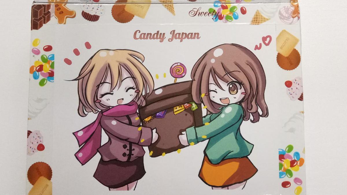 Dwie rysunkowe bohaterki naklejki na paczce z Japonii trzymające pudełko ze słodyczami