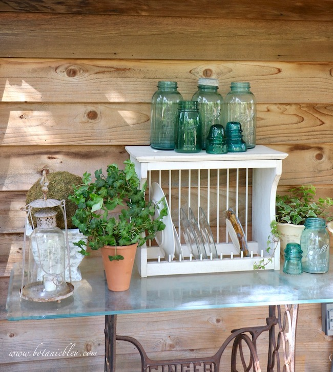 An outdoor table made using a repurposed Singer sewing base and a glass top is the solution for extra storage space