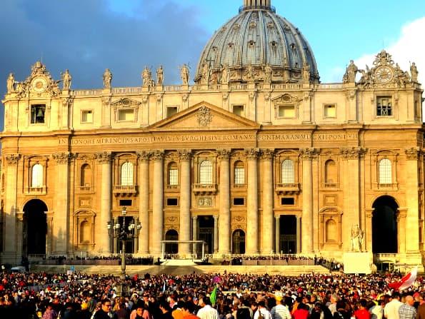 A imagem mostra a fachada de uma grande igreja e a calçada lotada de pessoas com os mesmos interesses.