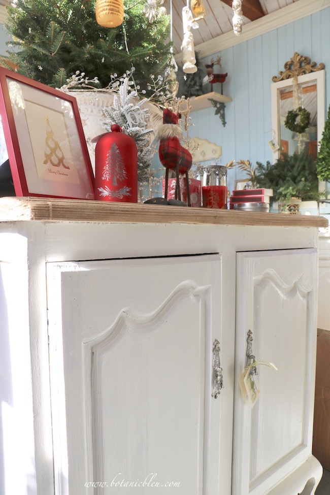 French Country Christmas Event 2019 has a French country style white cabinet with red Christmas decor on its wood top