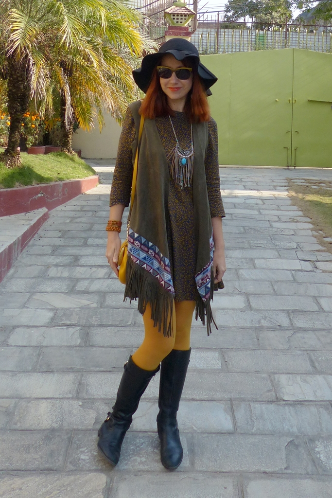 Long fringed vest worn over mini dress accessorized with mustard tights, tribal necklace and hat