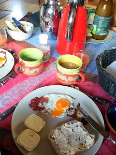 Ein fröhlich bunter Frühstückstisch mit von Künstlerhand getöpferten Bechern.