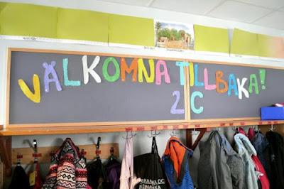 """det står """"välkommen tillbaka 2 c"""" på svarta tavlan i skolsalen"""
