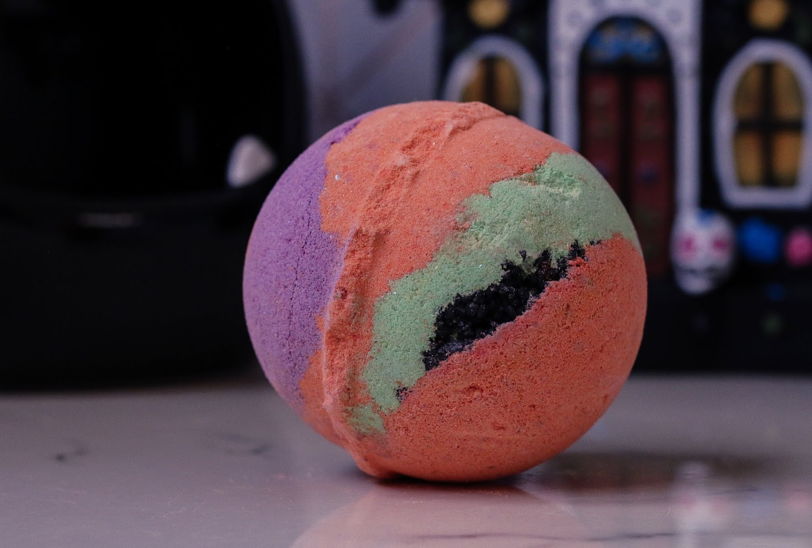 Close up photo of the Mercury Retrograde Bath bomb from lush. A round orange bath bomb with green, purple and black coarse sea salt through it. Bath bomb sitting on white marble bed side table with a Haunted house Halloween decoration in the background.