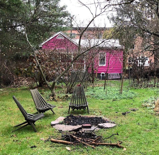 pink house behind large backyard with fire pit
