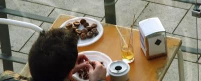 homem comendo castanhas assadas em mesa de bar