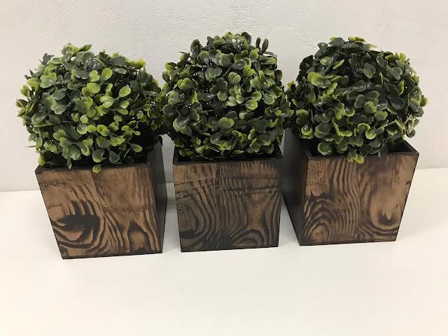 Três cachepots com pintura imitando madeira e plantinhas artificiais do tipo buxinho.