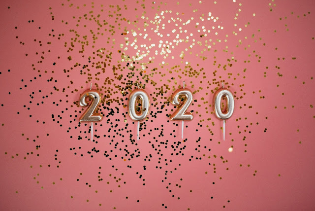 "Gold number candles spelling ""2020"" against a pink background."