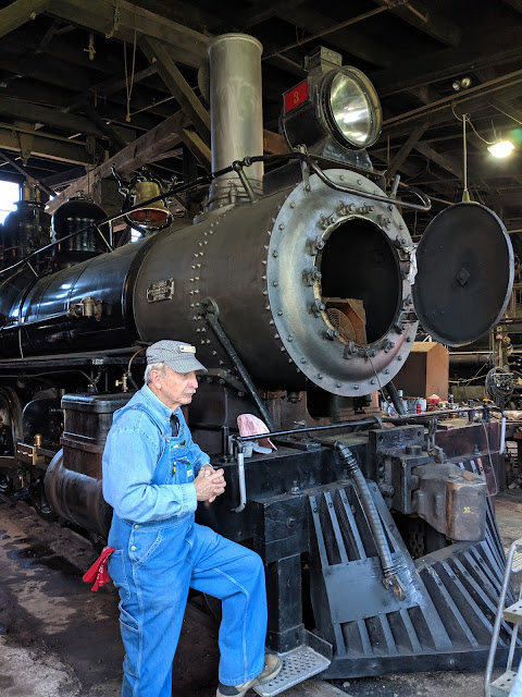 A docent in denim coveralls with a red bandana and a railway cap stands with his foot on the rail as he talks about this engine.