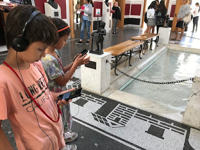 Children listening to an audio guide at a museum