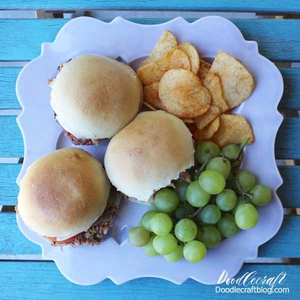 10 Quick Dinner Ideas for Back-to-School, featuring pulled pork sandwiches with sliced tomatoes, chips and green grapes.
