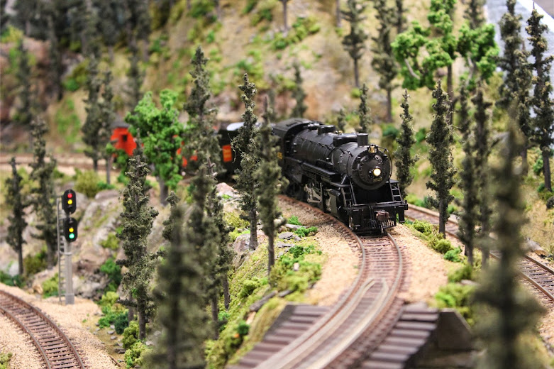 A USRA Light Mikado 2-8-2 steam locomotive approaching a wooden train trestle