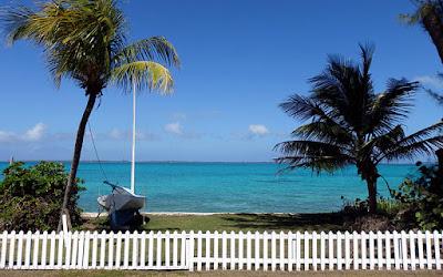 Sailboat ashore on white picket fence property.