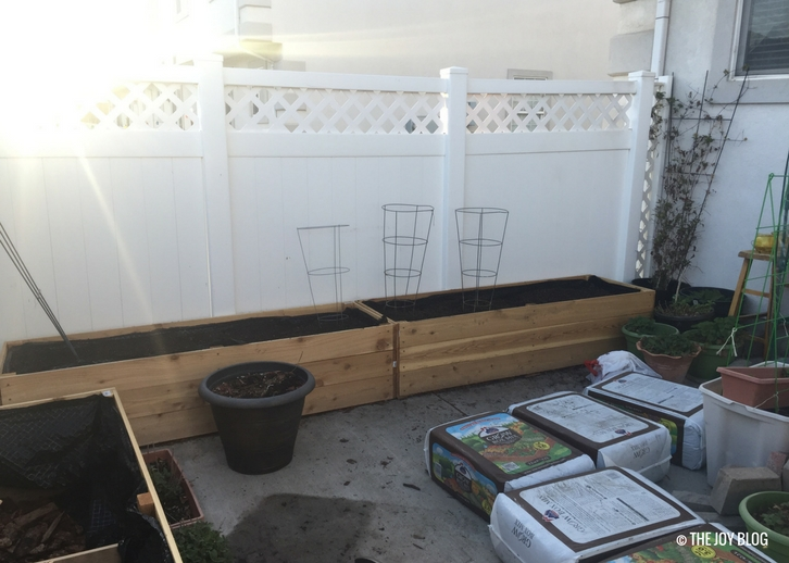 Messy patio with brand new raised beds with fresh new soil, ready for planting. // www.thejoyblog.net