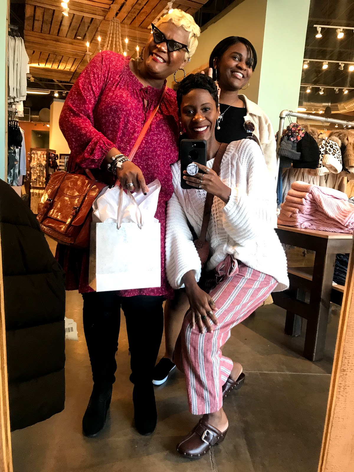 Tangie Bell taking mirror selfies with her daughters, shopping at the clothing stores.
