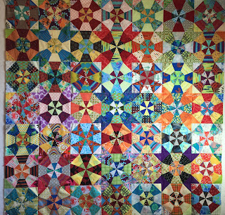 Brightly colored fabrics and tulip-like extensions make a lively kaleidoscope quilt