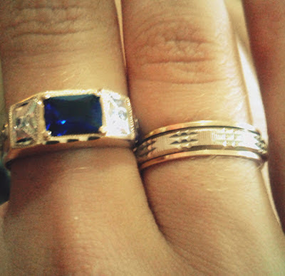 A foto mostra o anel de formatura de Filosofia em pedra azul e ao lado os emblemas especificísticos do curso.