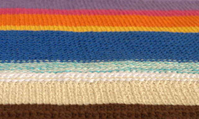 Looking across a placemat from bottom (foreground) to the top (distance) the colours are brown, beige, white, variegated white/aqua, royal blue, golden yellow, orange, hot pink and lavender.