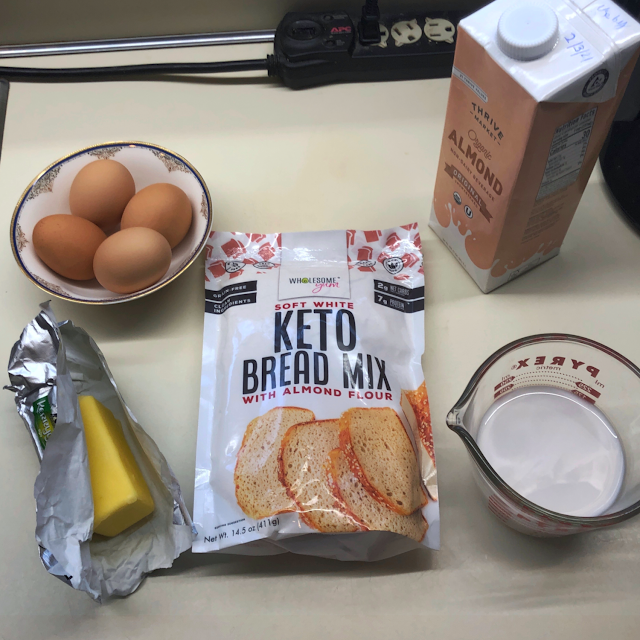 Photo of ingredients to make Wholesome Yum Easy Keto Bread Mix: bag of mix, 6 tablespoons of butter, 4 eggs, and 3/4 cup almond milk