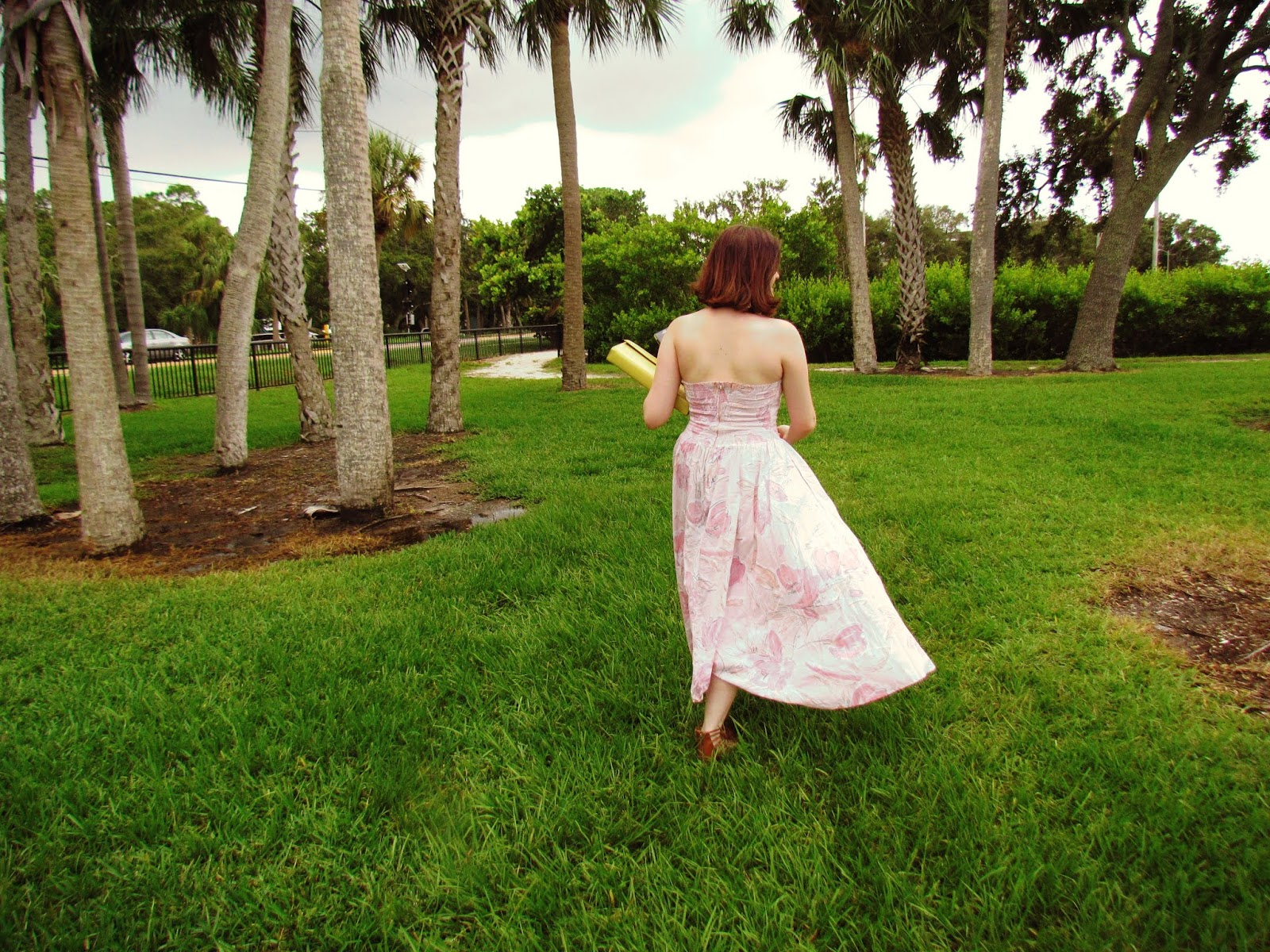 Young brunette girl in vintage peach flower gown on dark green grass by a marina in Florida + Florida Living