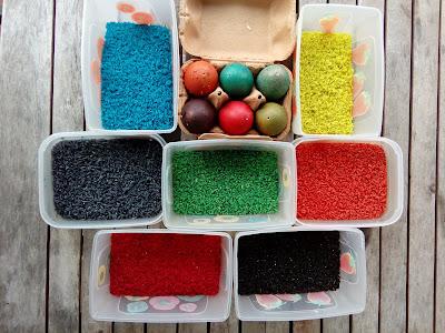 Ovos pintados rodeados de caixas de arroz colorido