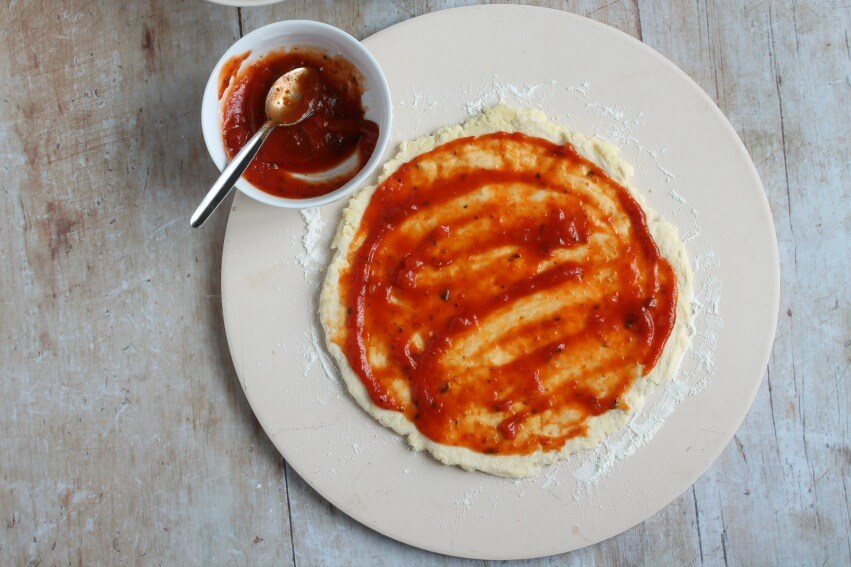 Spreading tomato puree onto scone pizza base