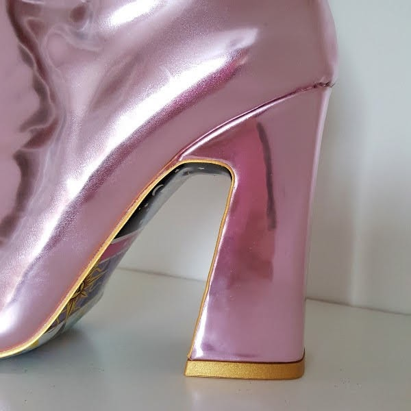close up of chunky angled heel on pink metallic ankle boot