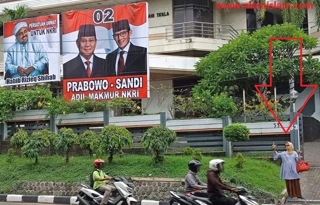 The power of emak-emak. Wanita ini pasang spanduk raksasa Prabowo Sandi dan acungkan dua jari seharian di pinggir jalan.