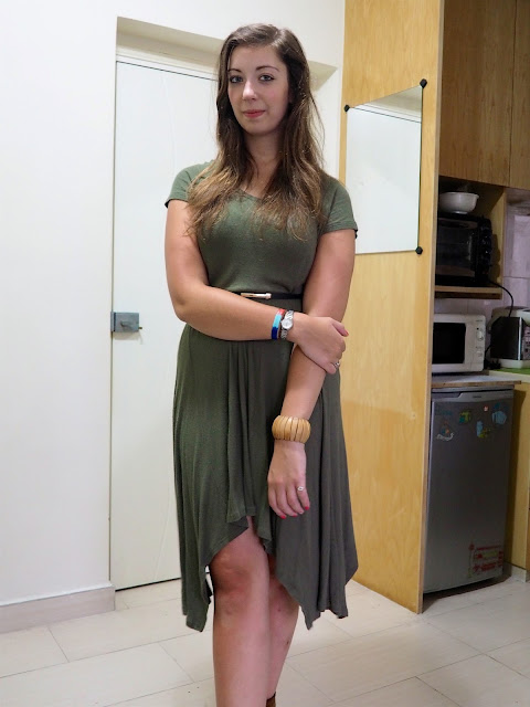 In the Jungle   work outfit of long, loose, forest green dress with belted waist and brown chunky wooden bracelet
