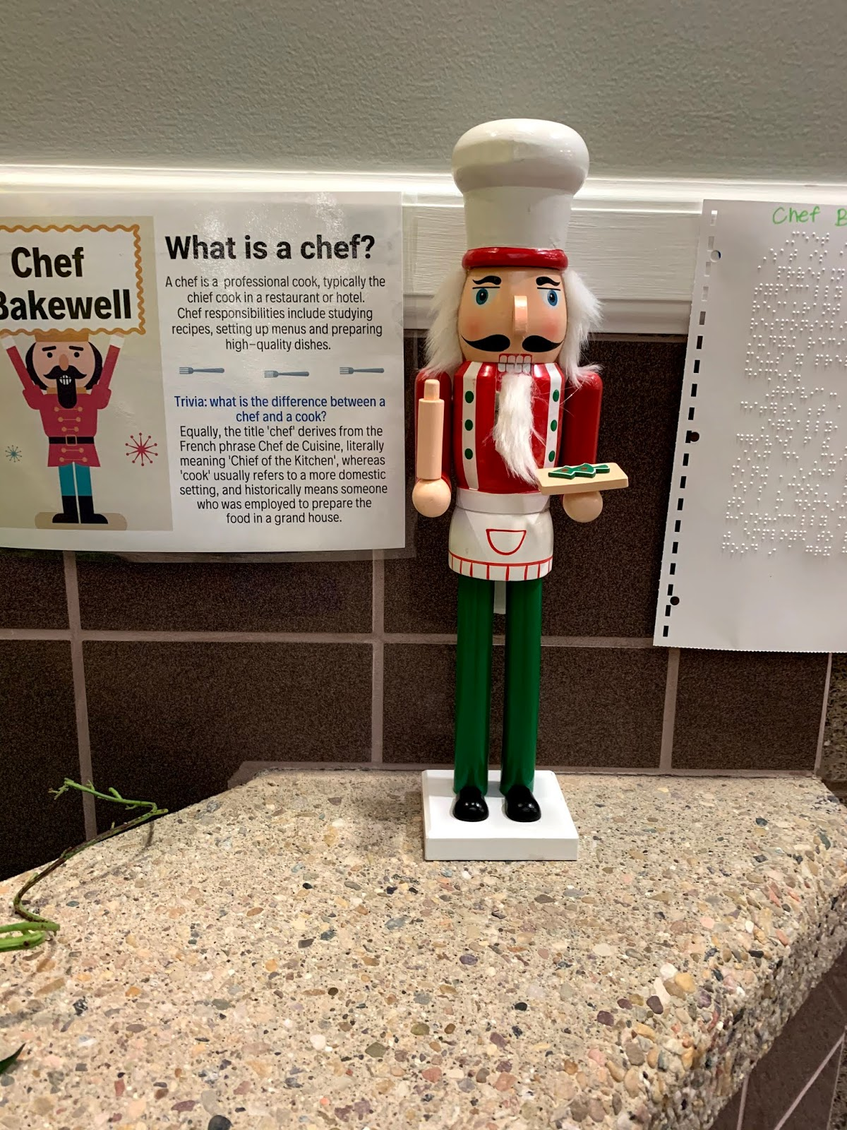 A chef  Nutcracker with a game sign in Braille and print.