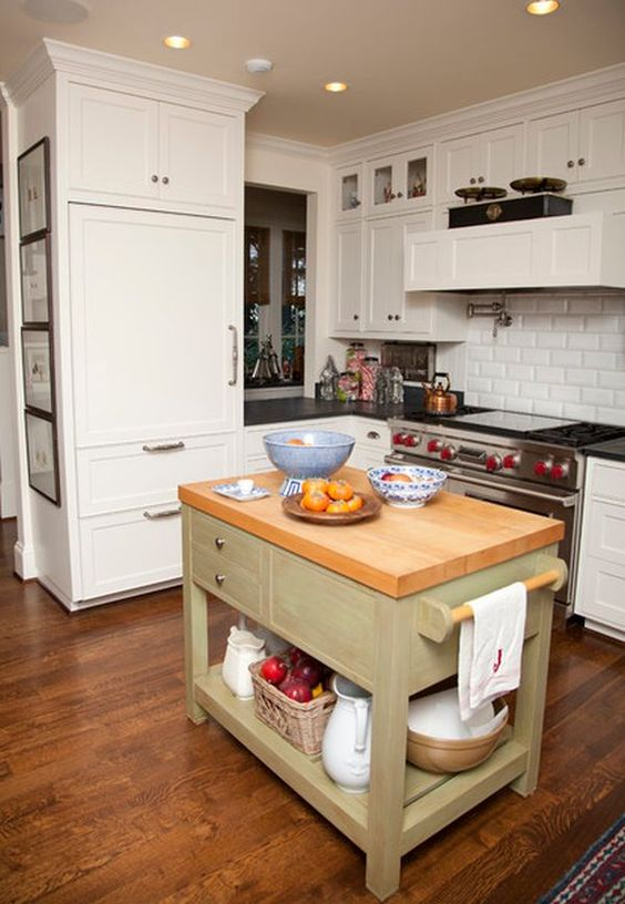 an olive green kitchen island with a wooden countertop drawers and open storage in rustic style