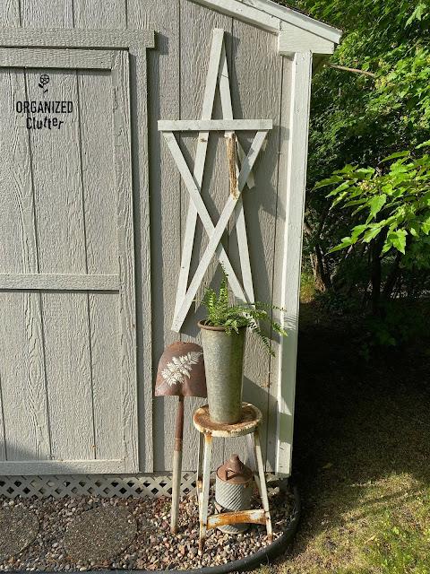 Photo of a fern on rusty stool with a fern stenciled shovel head