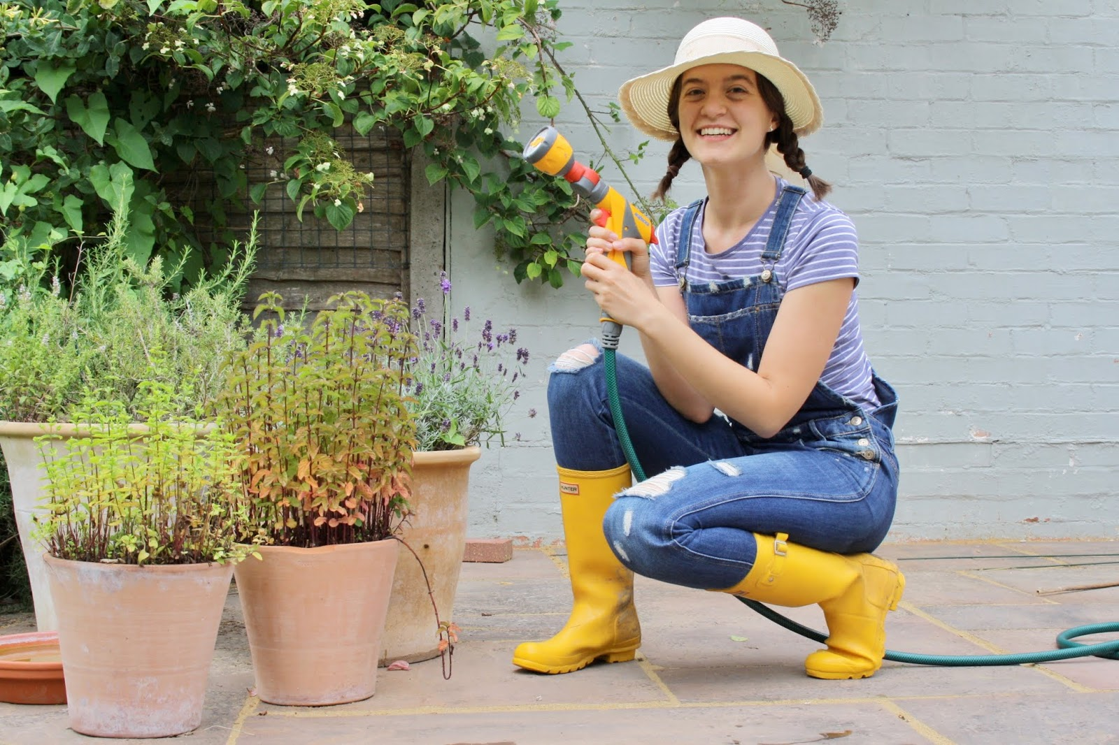 Abbey, crouching down on one knee, holds a hose next to some pot plants. She wears denim dungarees and yellow wellies