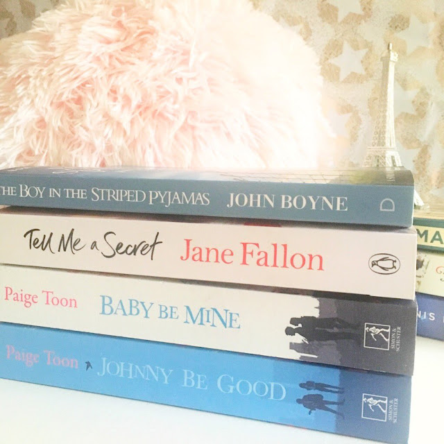 stack of books in front of pink fluffy pillow and eiffel tower ornament in the background. Johnny Be Good, Baby Be Mine, Tell Me A Secret, The Boy In The Striped Pyjamas