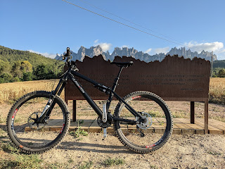mountain bike in front of bench and mountains