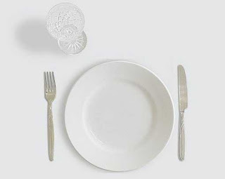 Empty white plate with a knife and fork