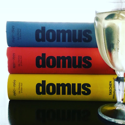Stack of three domus books and a glass of wine on a coffee table.