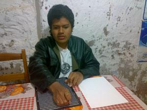 Edson Estrada escribiendo con pauta y punzón