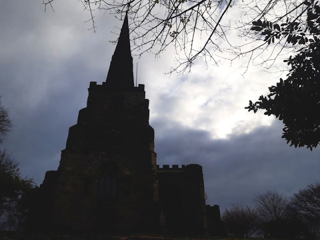 Image shows the silhouette of a church against a gloomy grey sky