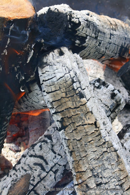 Another view of the campfire, black and white textures of wood logs turning to coals, with flames dancing around the edges of the wood.