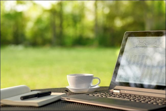 كمبيوتر محمول وقهوة على طاولة في الهواء الطلق
